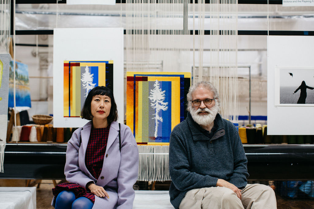 Eugenia Lim and Tim Gresham in front of the 'Fossil Futures (Old Tjikko)' tapestry, designed by Eugenia Lim in 2021. Photograph courtesy of Marie-Luise Skibbe.