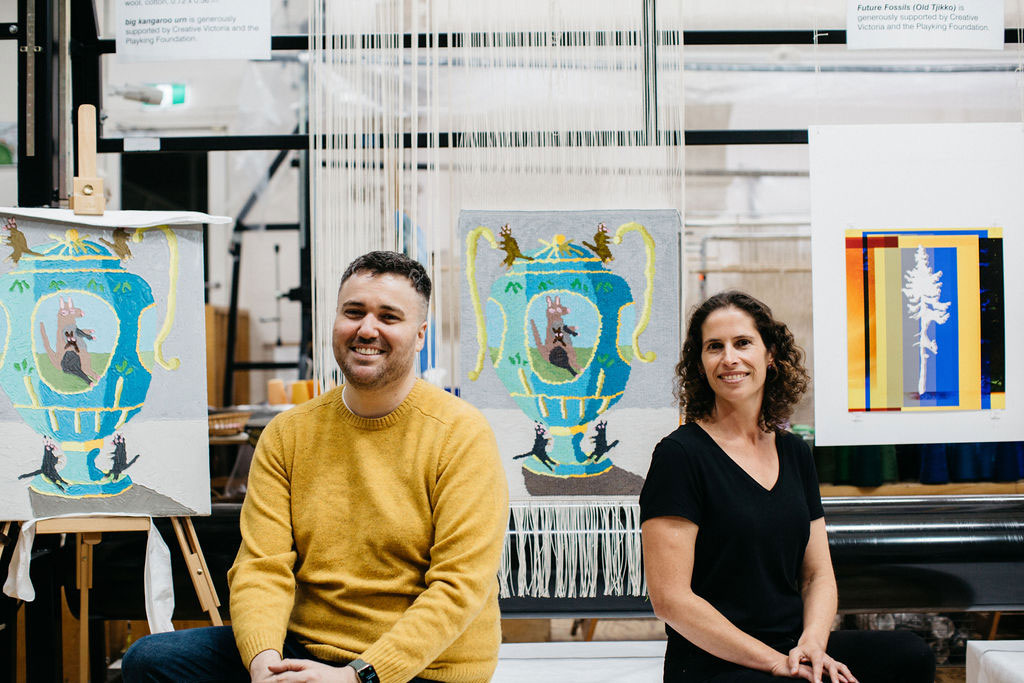 Troy Emery and Emma Sulzer in front of the 'big kangaroo urn' tapestry, designed by Troy Emery in 2021. Photograph courtesy of Marie-Luise Skibbe.
