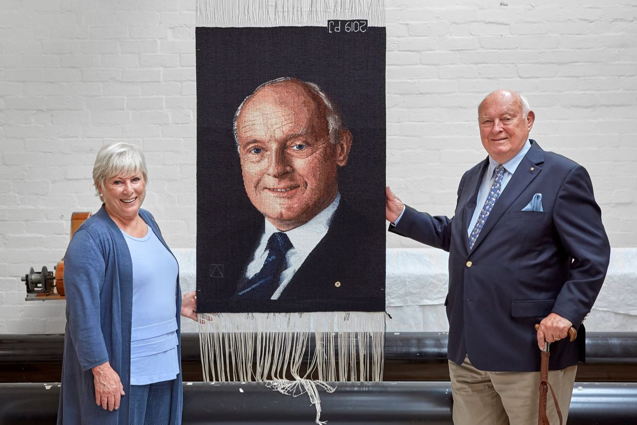 Lynn Rainbow-Reid AM and John B Reid AO with their commissioned tapestry, woven by Pamela Joyce at the ATW in 2019. Photo by Jeremy Weihrauch.
