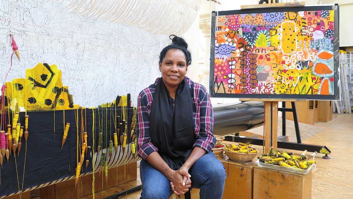 Artist Naomi Hobson in front of her design for 'The Royal Harvest' tapestry at the Australian Tapestry Workshop in 2021. Photo: ATW.